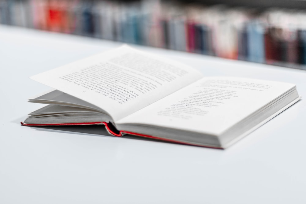 opened book on white surface