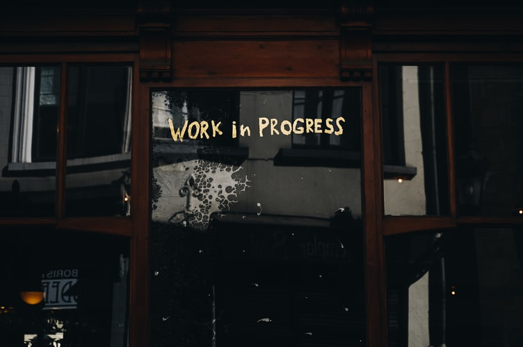 "A photo of a dark wood wall with an inset bed or day couch, above it written on the wall says ""work in progress"""