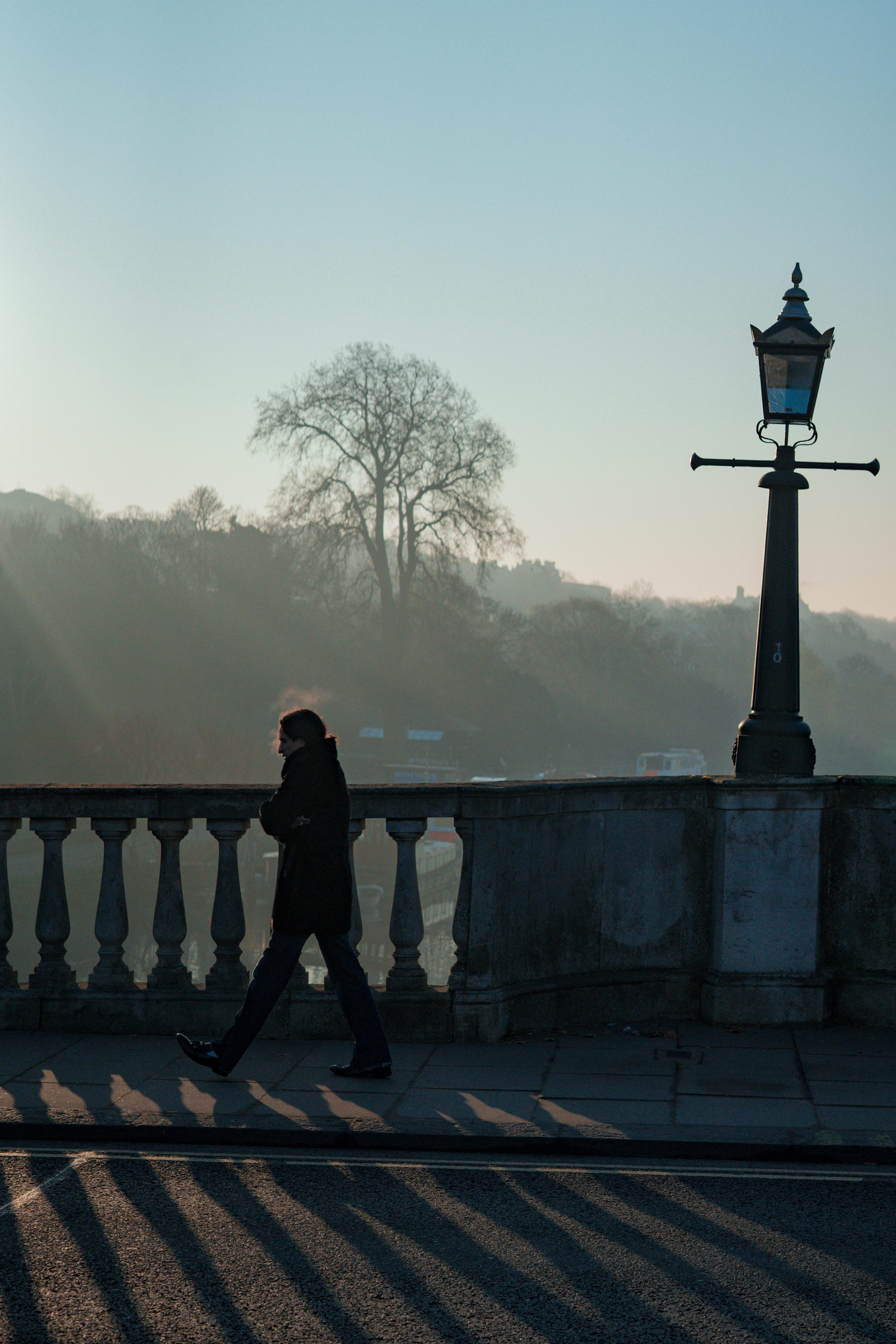 woman walking beside fence