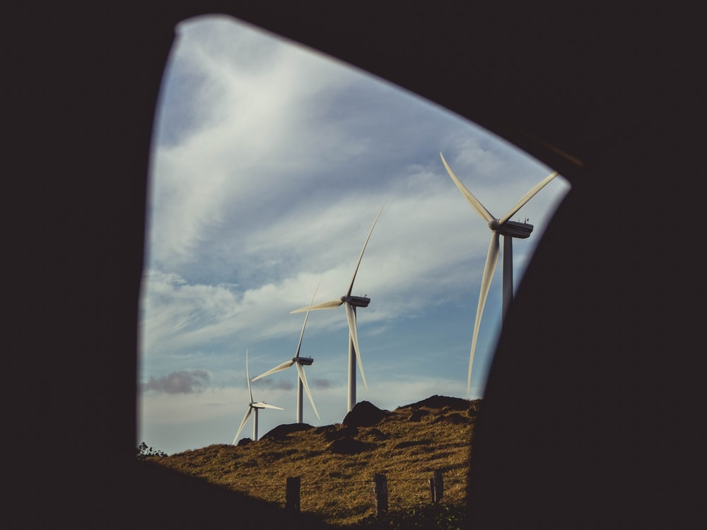 four gray windmills during daytime