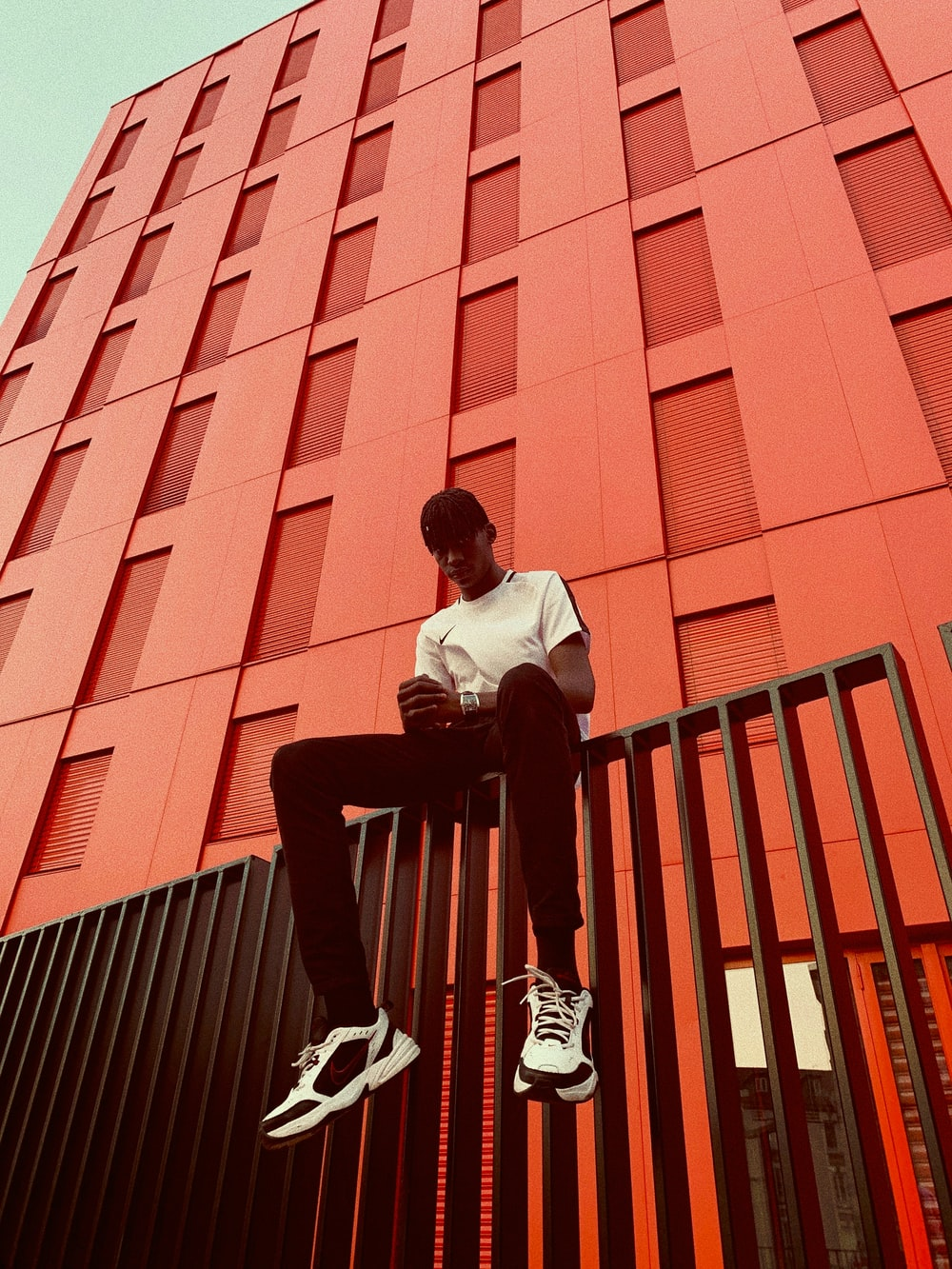 man sitting on black fence beside red concrete building