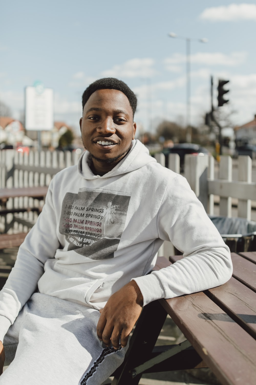 man wearing white pullover hoodie sitting on bencgh