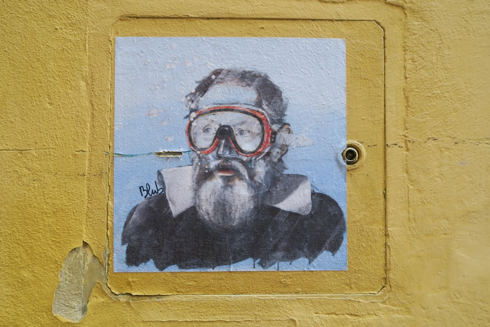 man wearing goggles painting