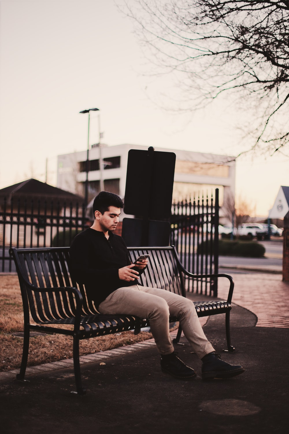 man sitting on black bench under withered tree