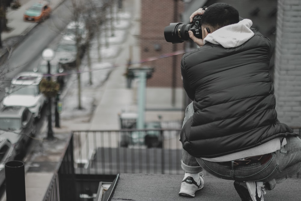 man taking photo of street on rooftop