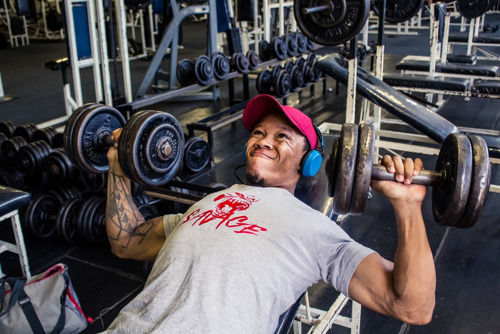 man in gray t-shirt doing dumbbell press