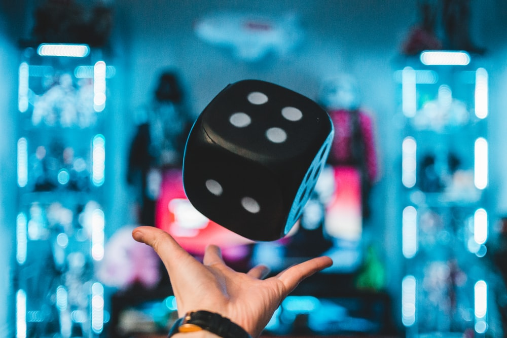 person's left palm about to catch black dice