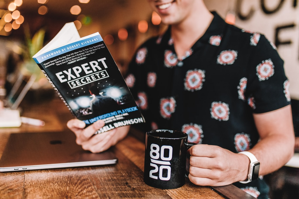 smiling man reading book while holding mug