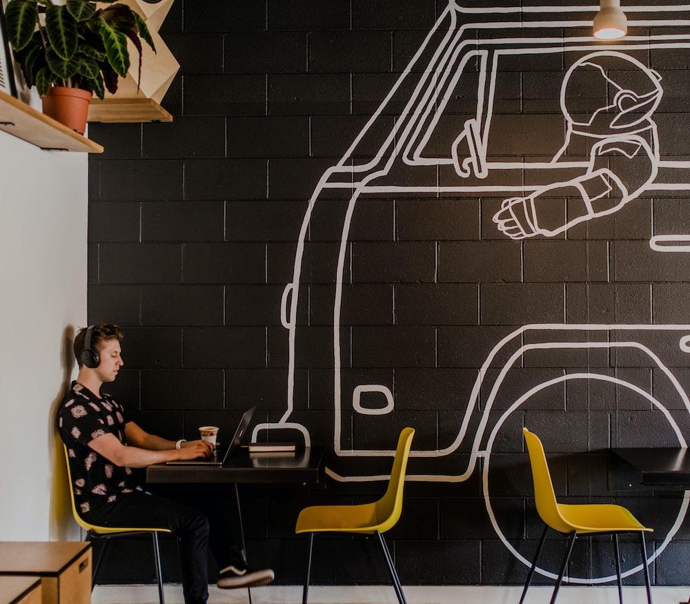 man wearing headphone using laptop while sitting beside table inside cafe