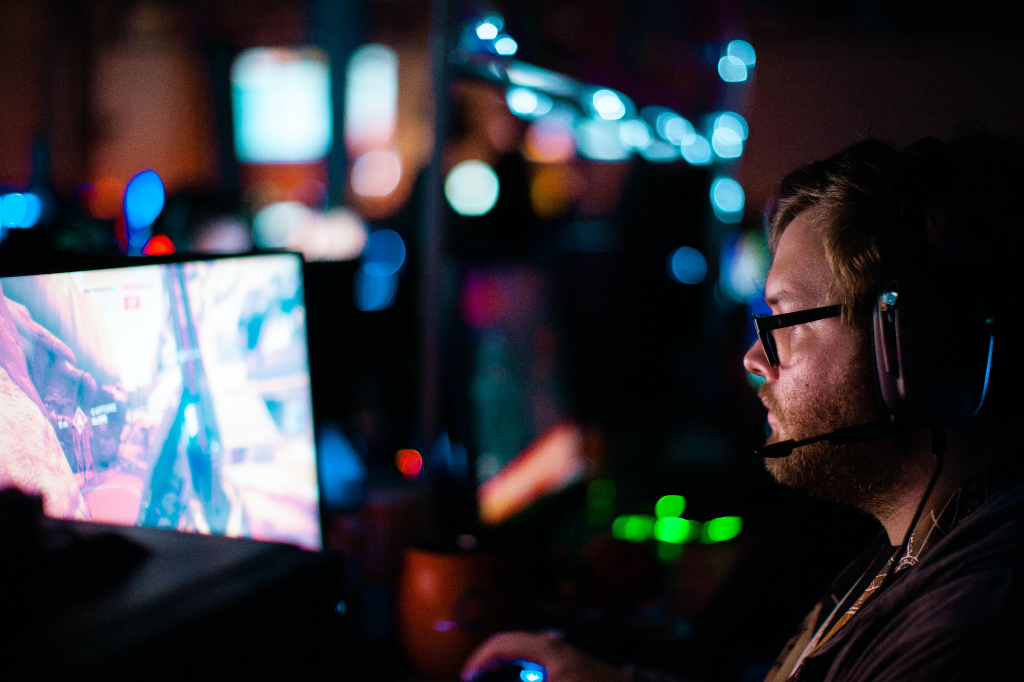 Man wearing headset playing a video game on a computer