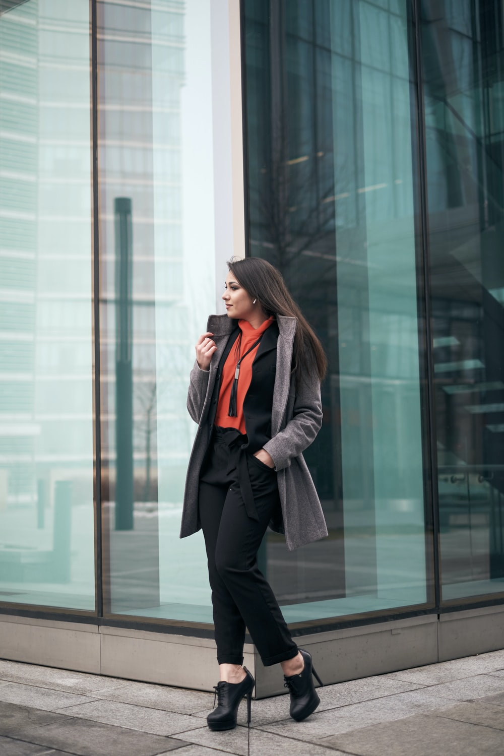 woman walking beside glass building