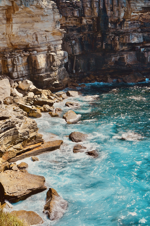 blue body of water near cliff