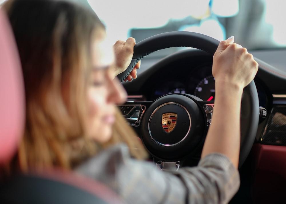 woman driving Porsche vehicle