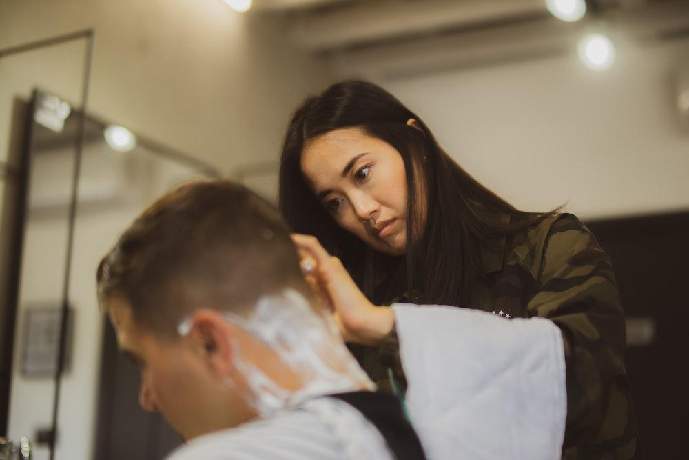 woman holding straight razor shaving man hair head