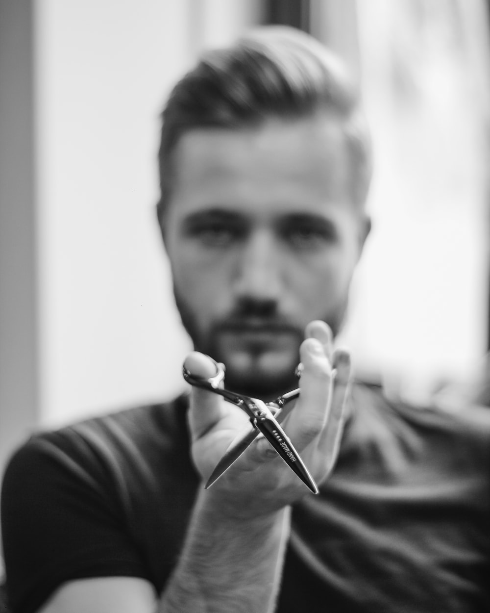 shallow focus photo of man holding scissors