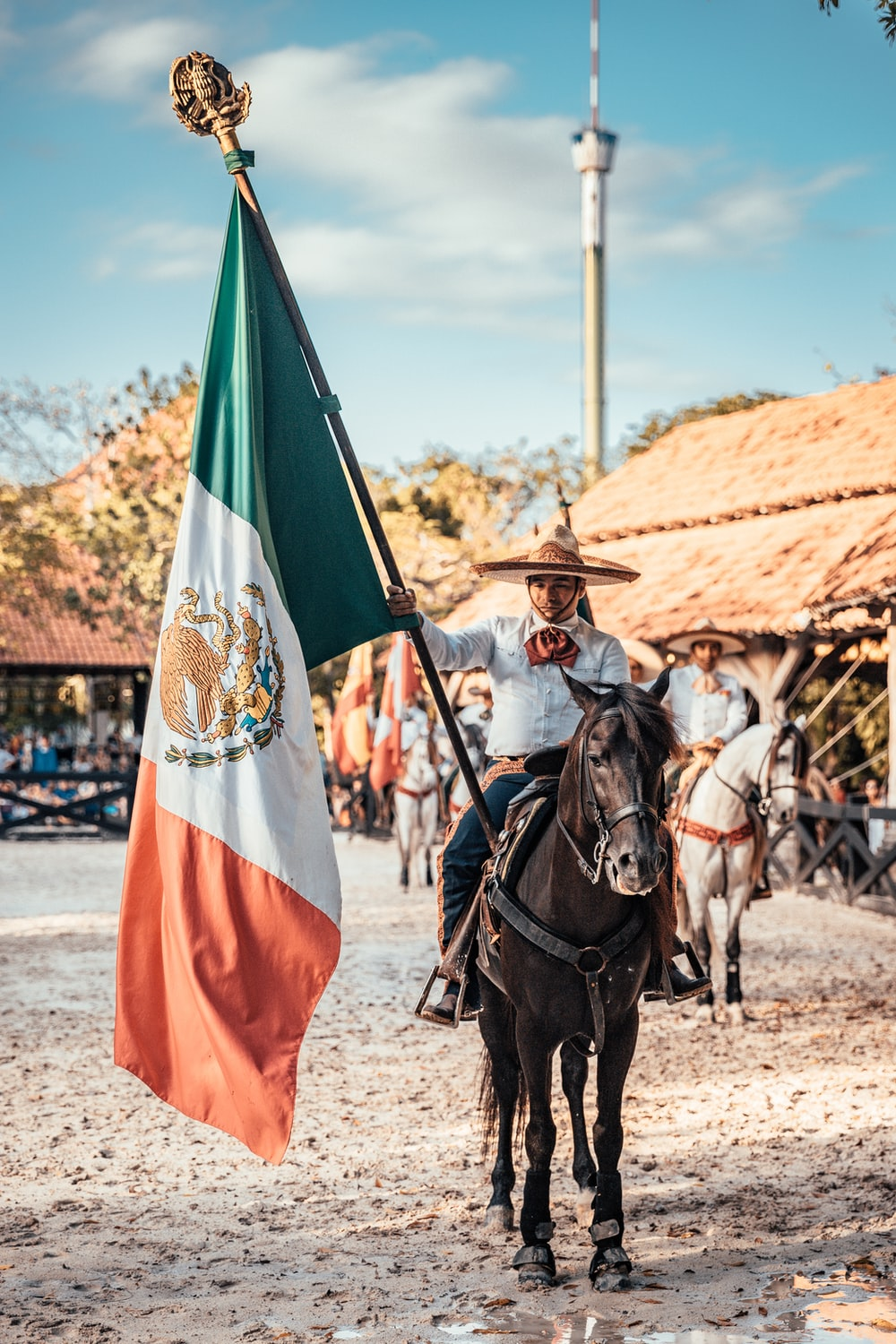 man riding on horse while holding flag of Mexico