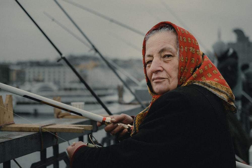 woman fishing on bridge during daytime