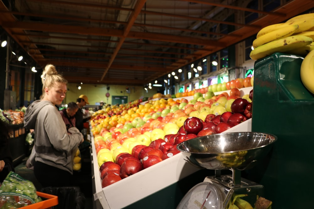 woman looking at displayed fruits