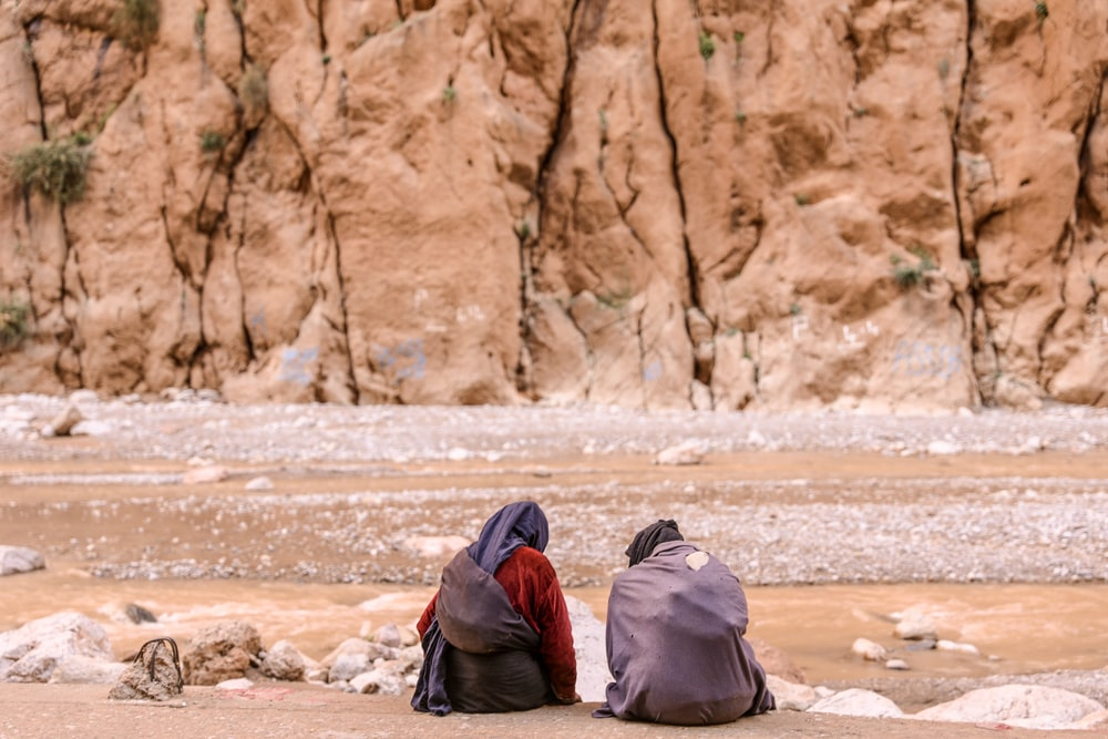 two person sitting on brown surface in front of mountain