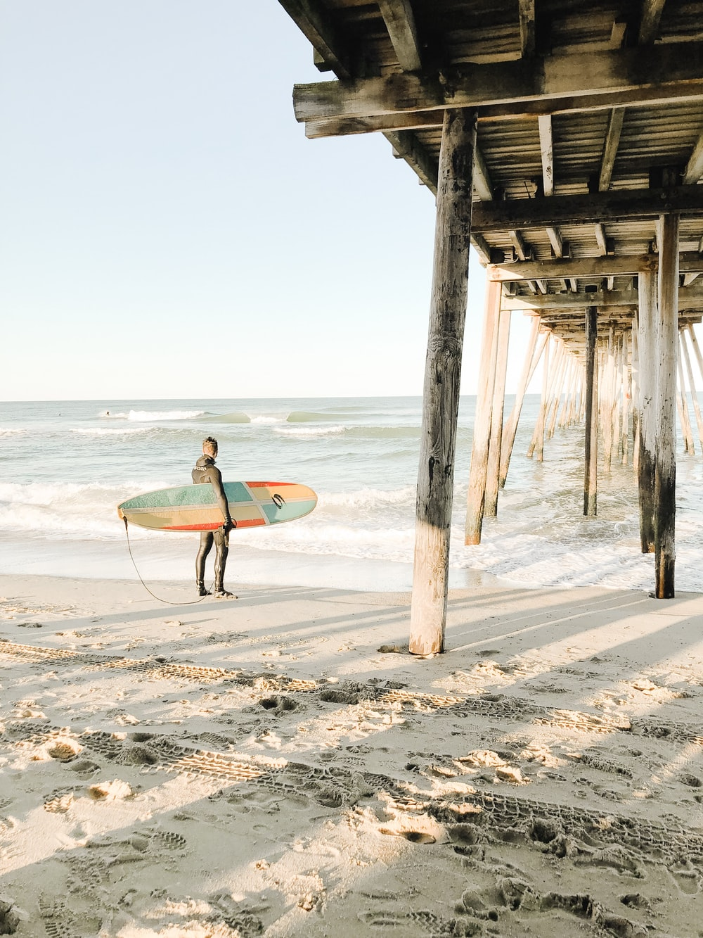 person holding surfboard while standing near brown wooden dock