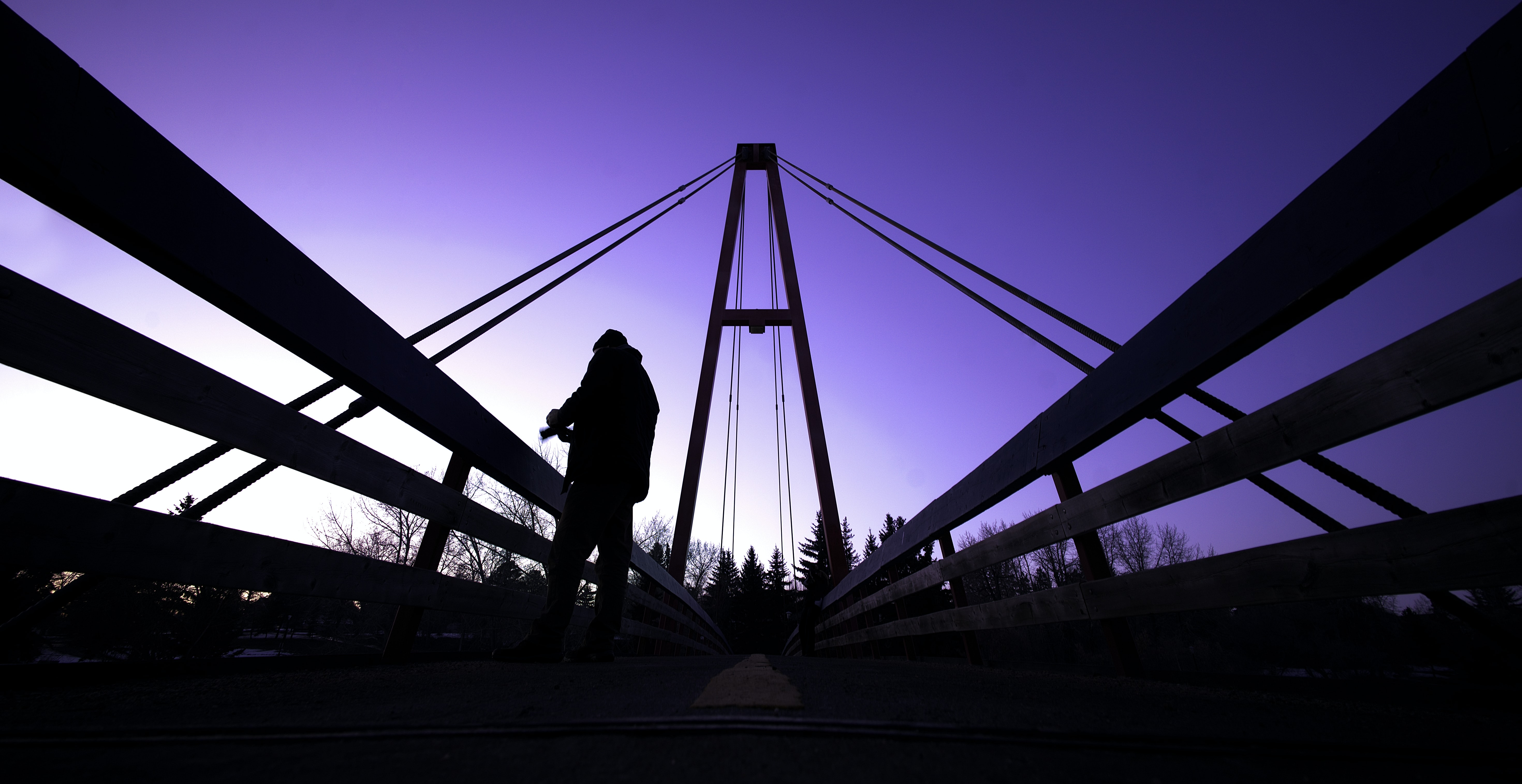 low angle photography of man standing on bridge
