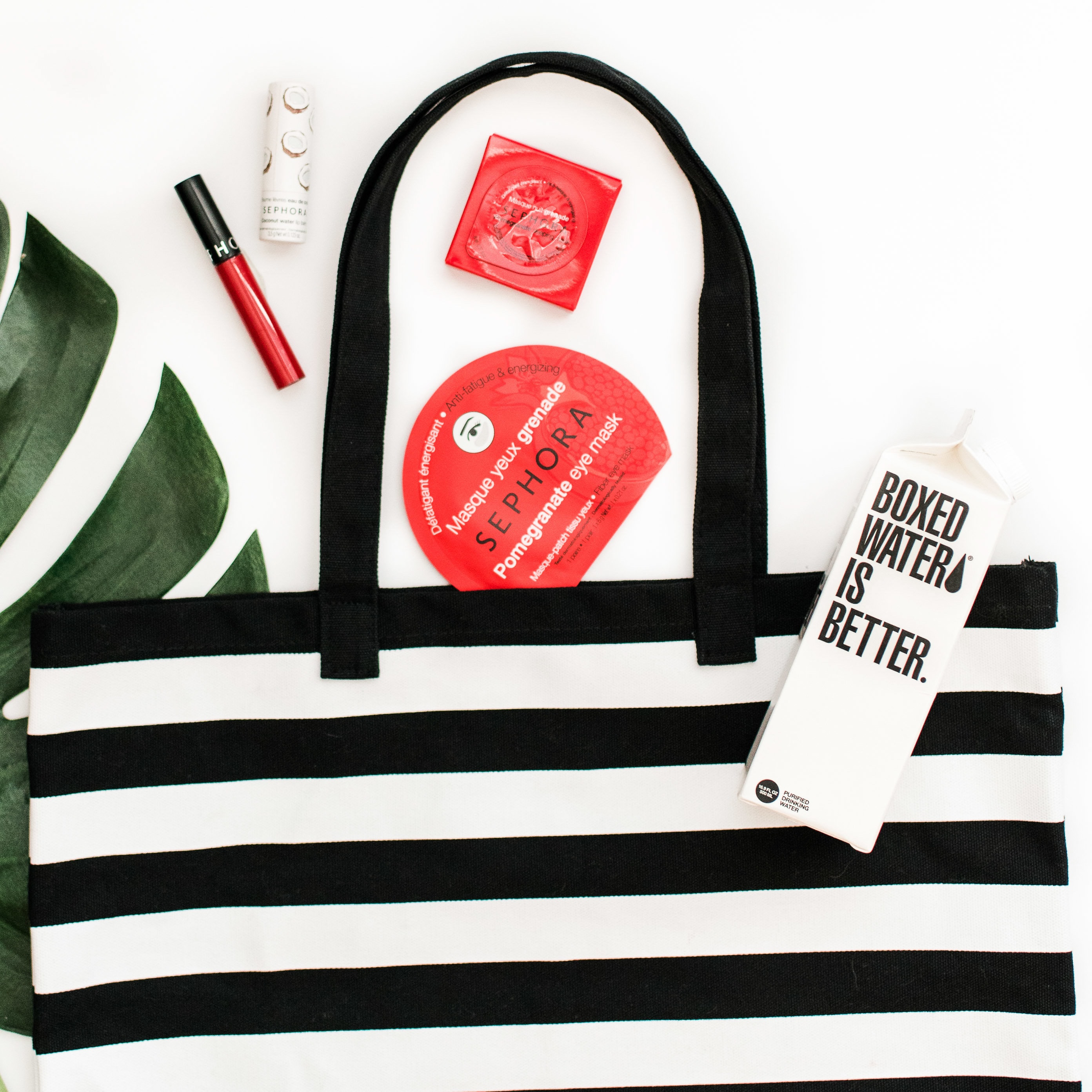 A black and white striped handbag with Sephora and Boxed Water products displayed next to it