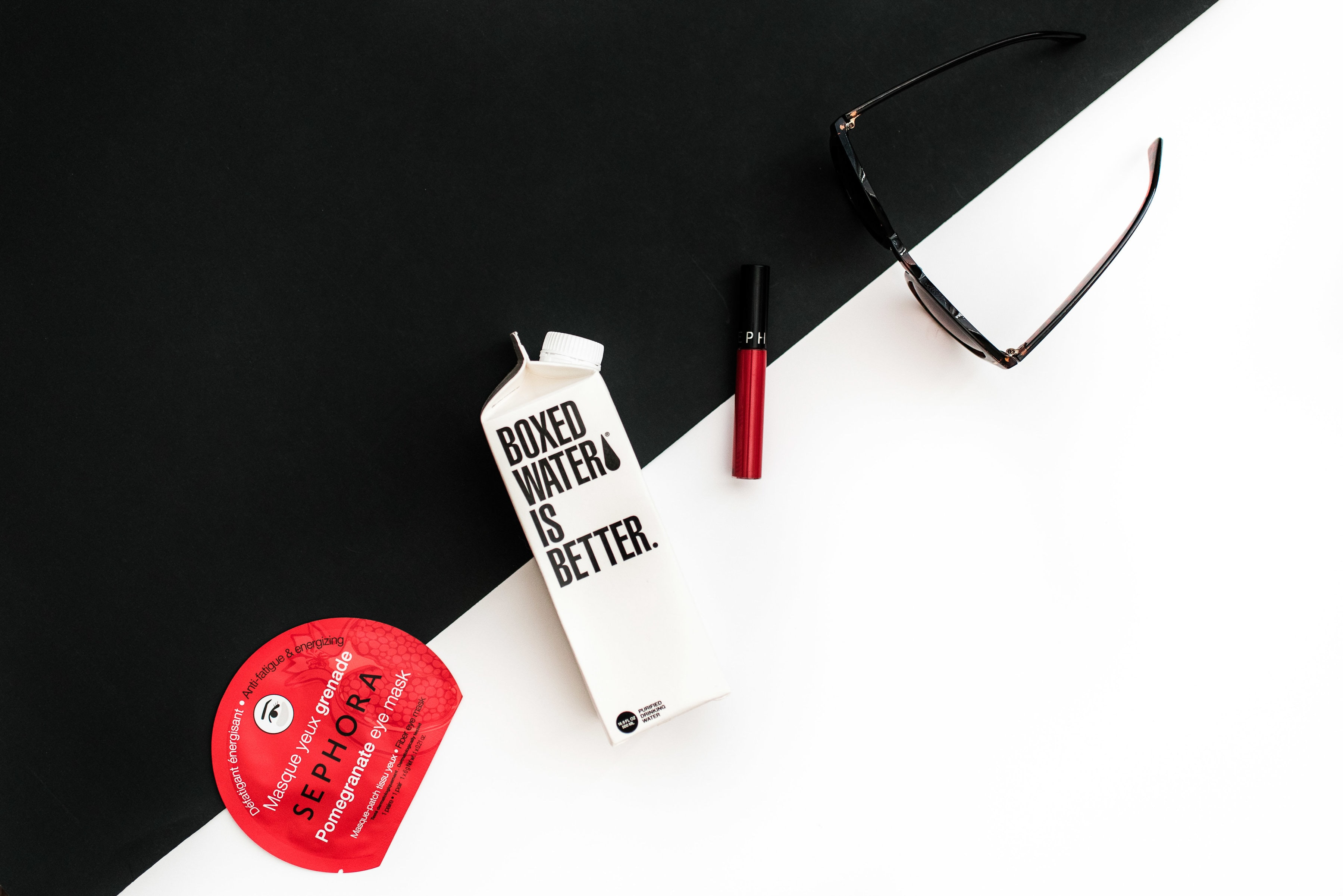 Sunglasses beside a carton of Boxed Water and Sephora products