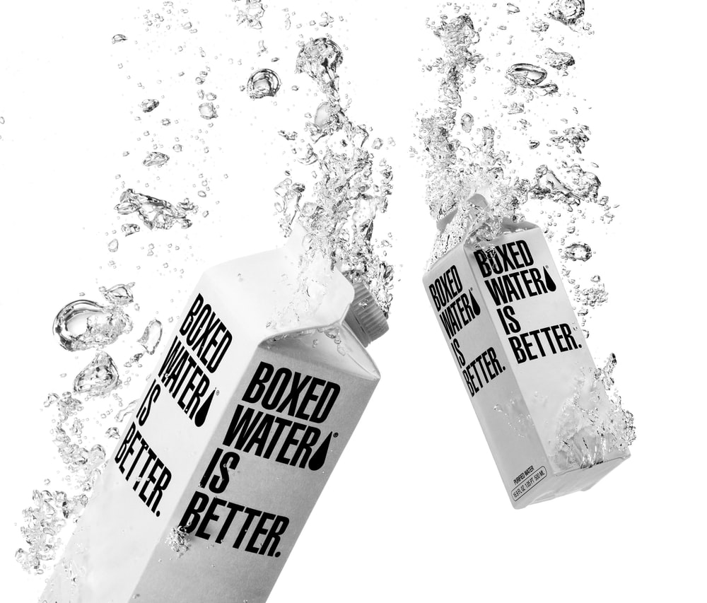 Two white Boxed Water cartons immersed in water
