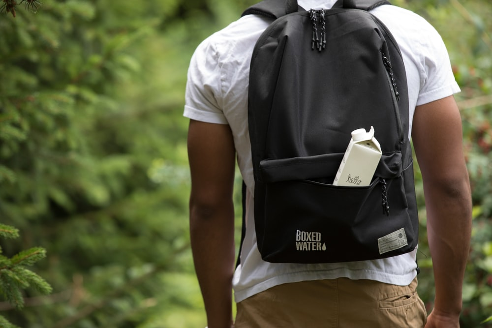 A man standing in the outdoors with a black backpack and a white Boxed Water box sticking out