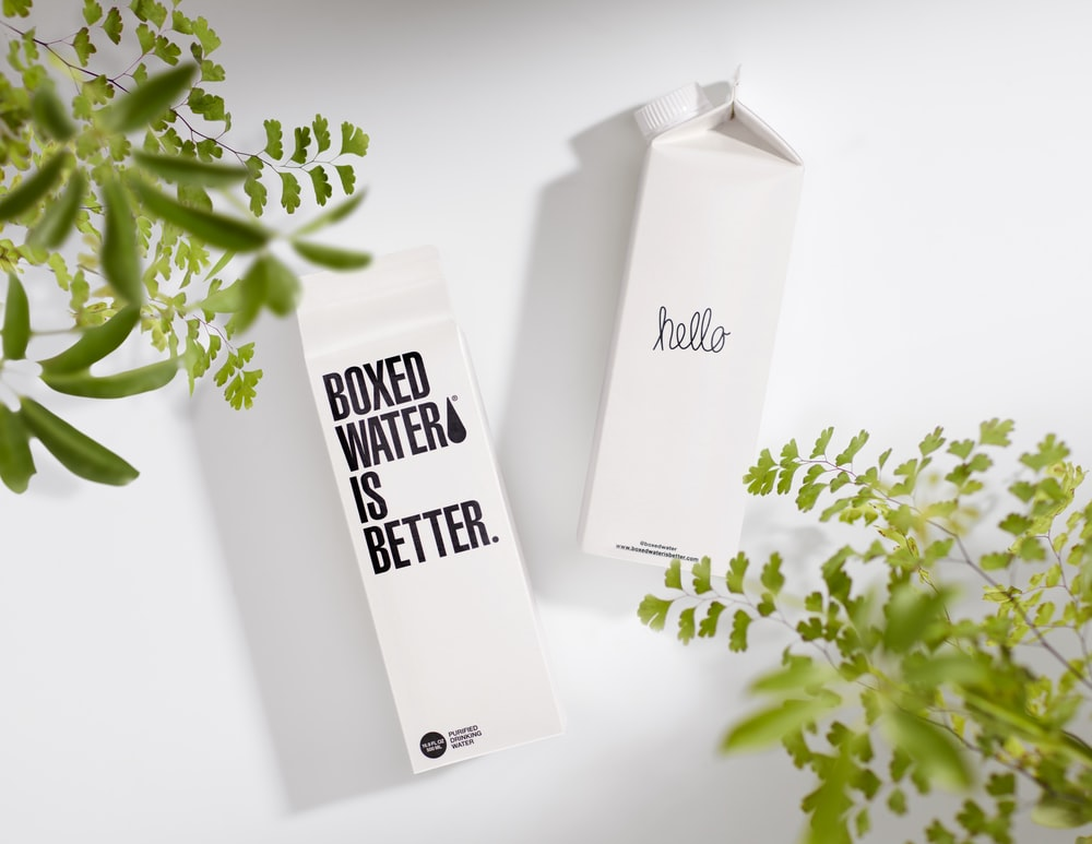 Two Boxed Water cartons on a white surface