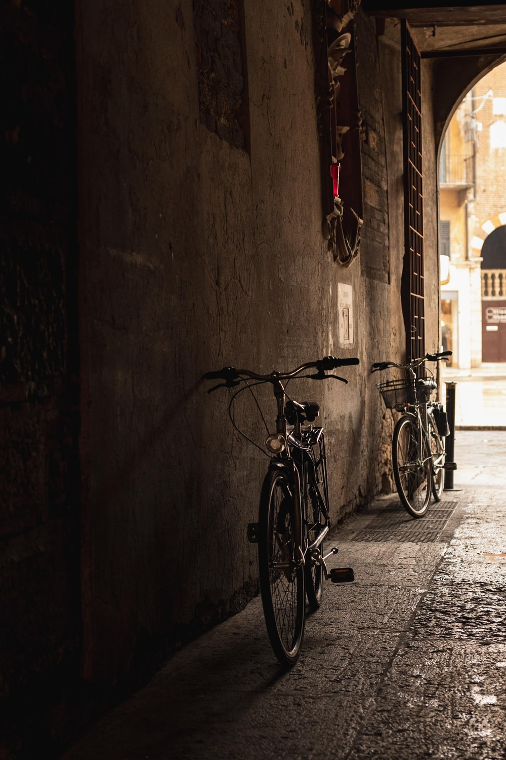 two black bicycles parked at wall during daytime