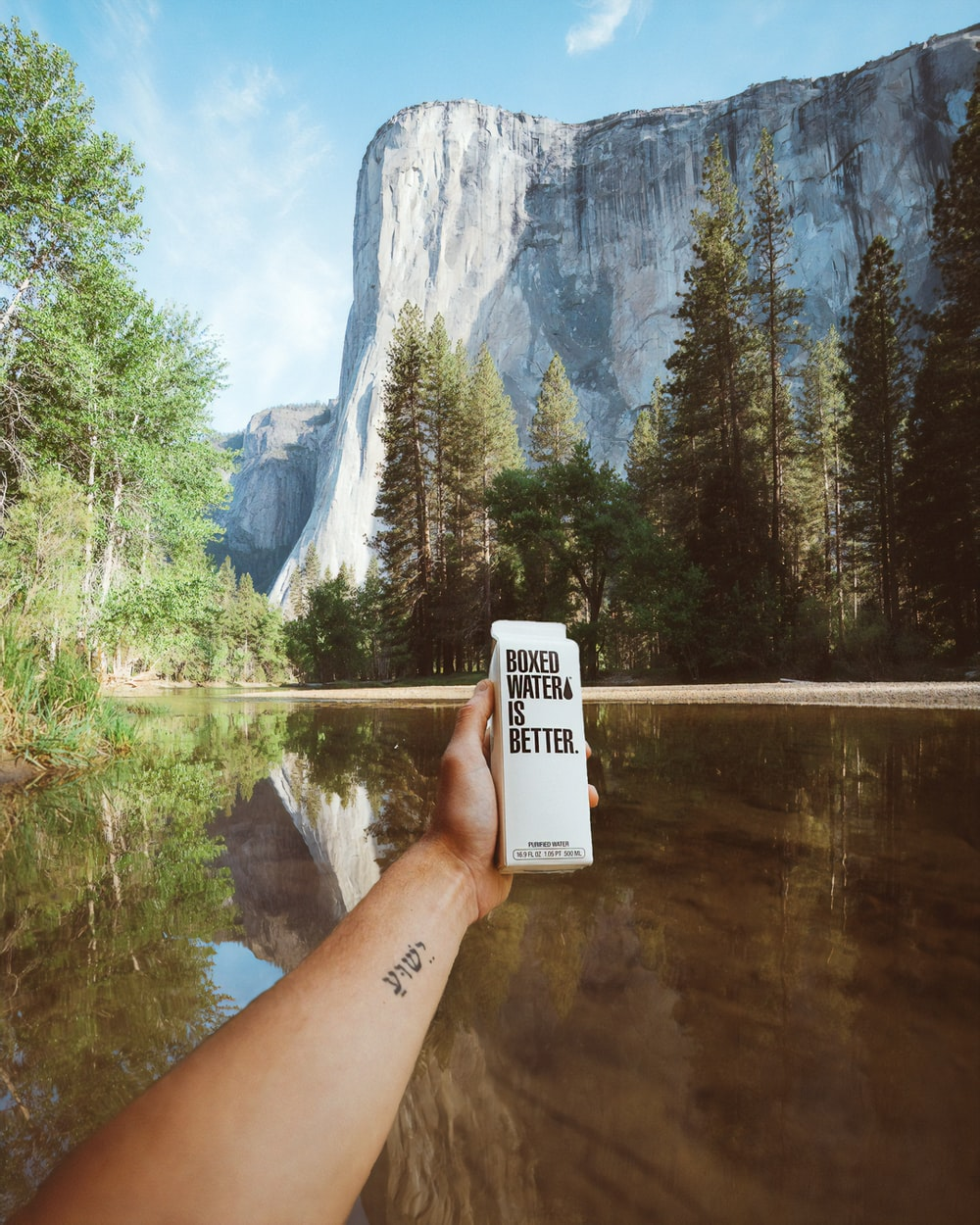 A person holding a carton of Boxed Water in their hand in front of El Capitan in Yosemite