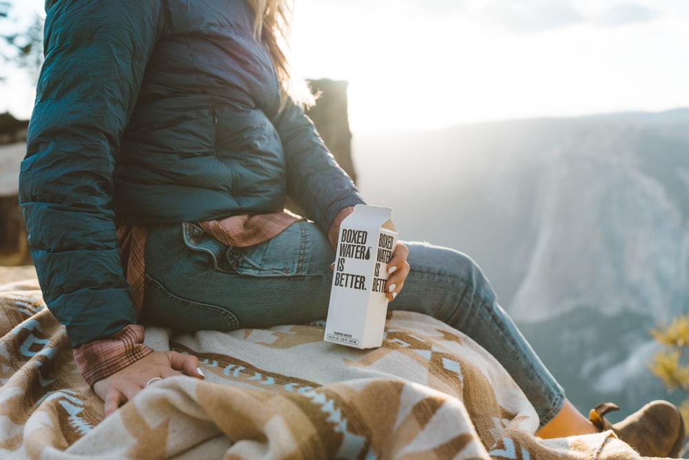A woman holding a white Boxed Water carton in Yosemite National Park