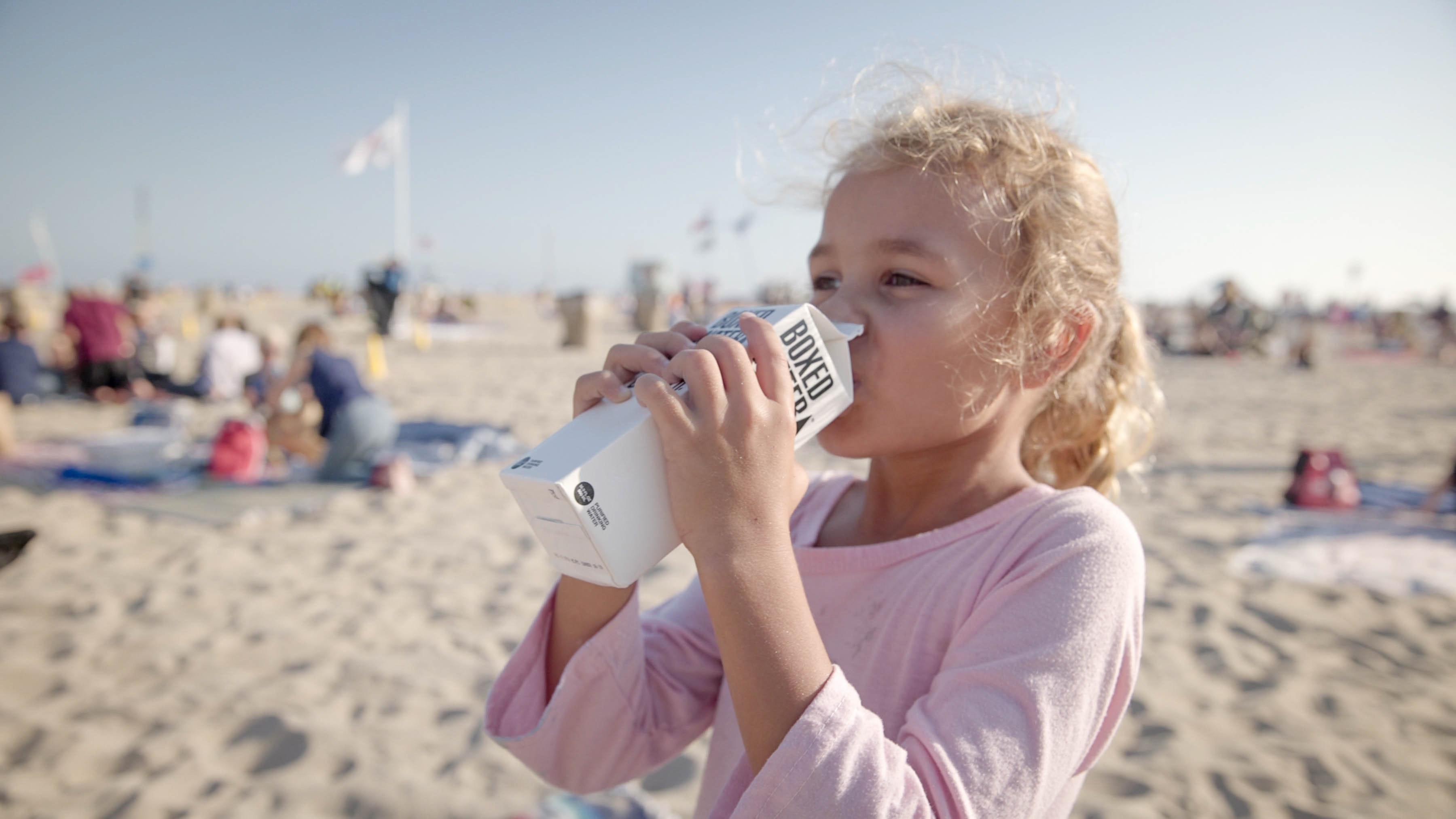 A girl drinking a carton of Boxed Water on the beach