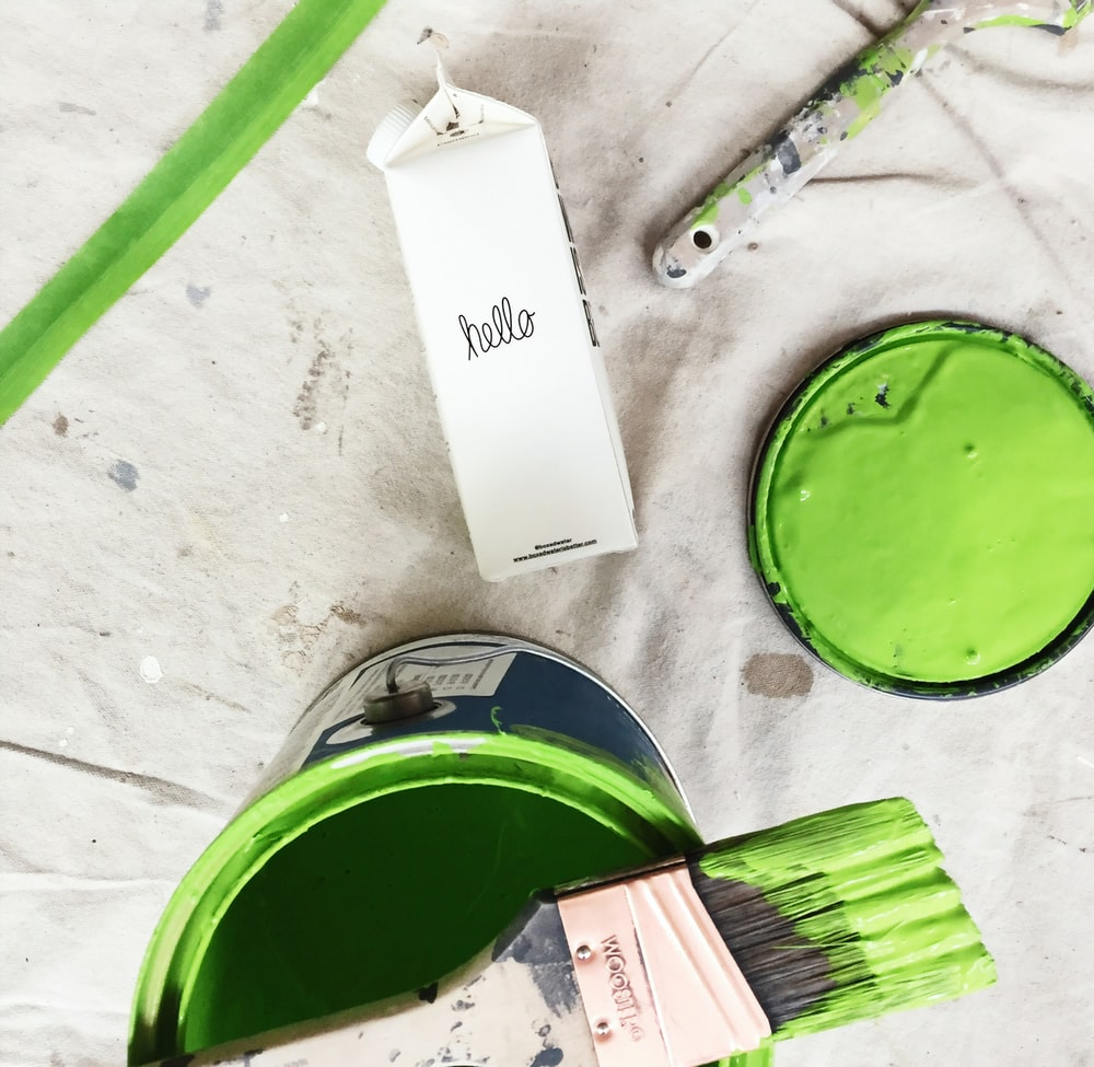 A green paint can and brush next to a carton of Boxed Water