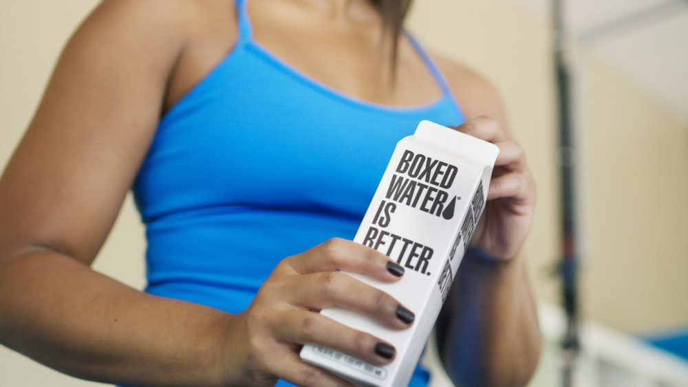 A woman holding a carton of Boxed Water while working out