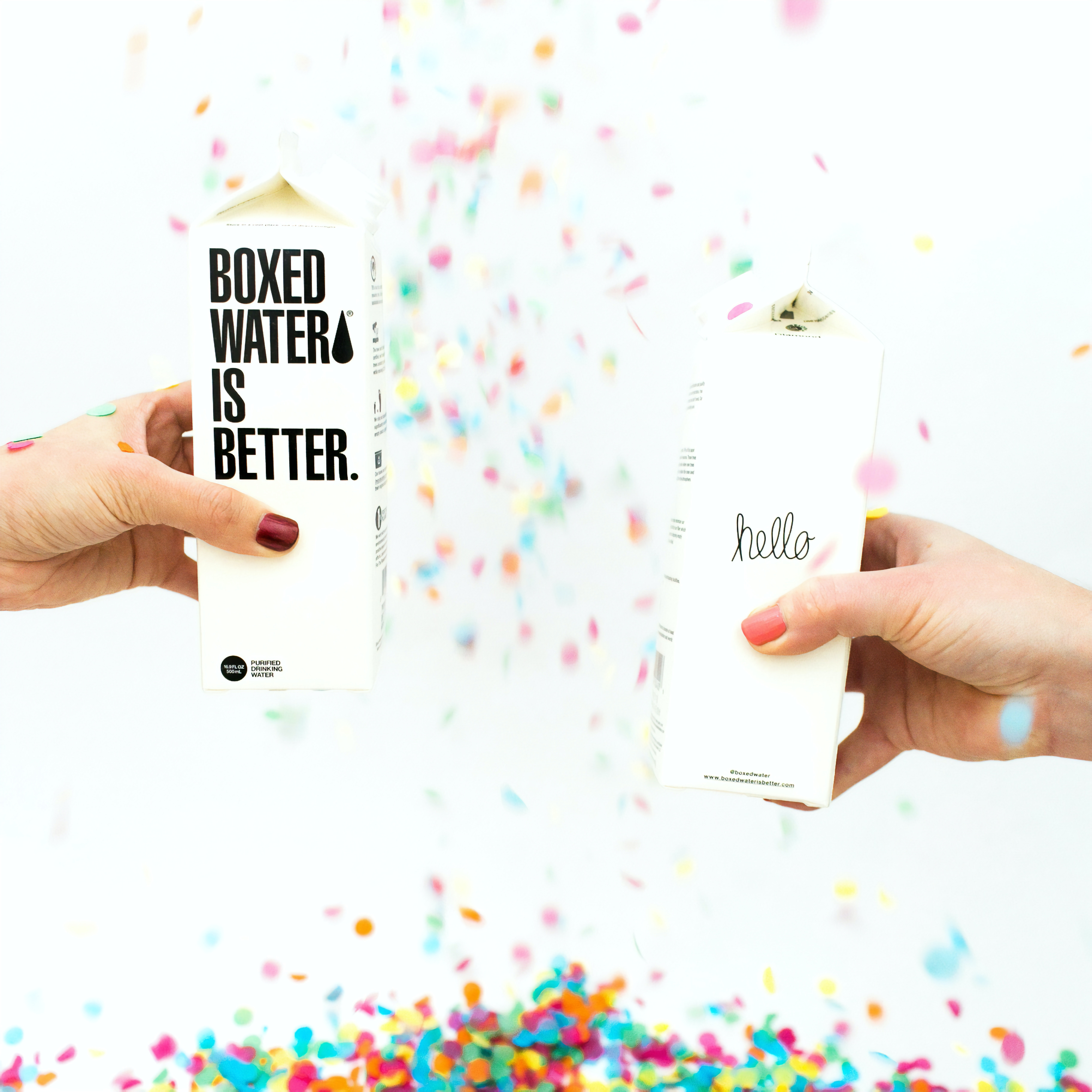 Two people holding Boxed Water cartons while confetti falls