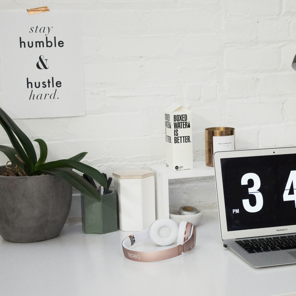 A MacBook Air sits next to headphones and a Boxed Water carton