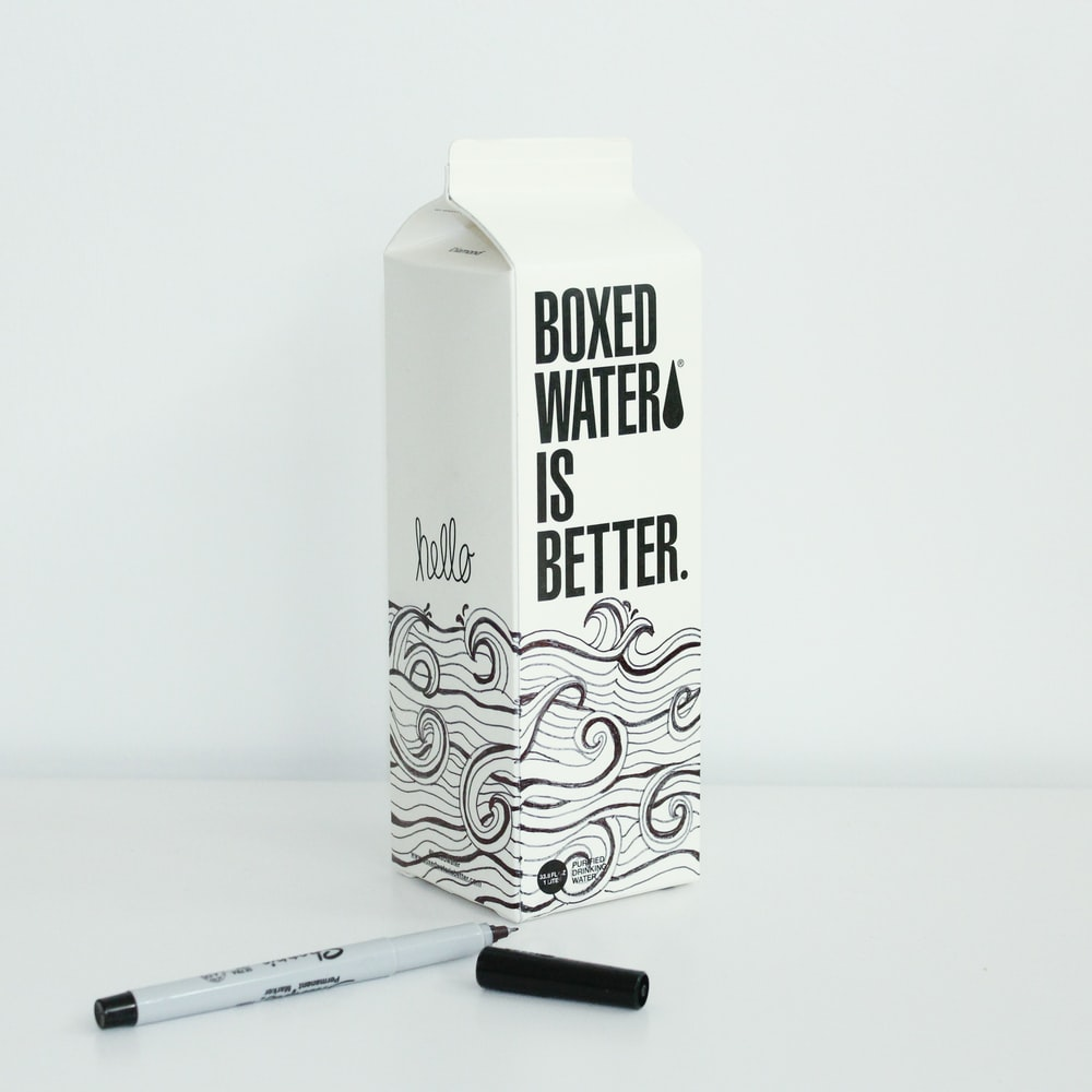 Boxed water is Better carton with waves drawn on it with a sharpie