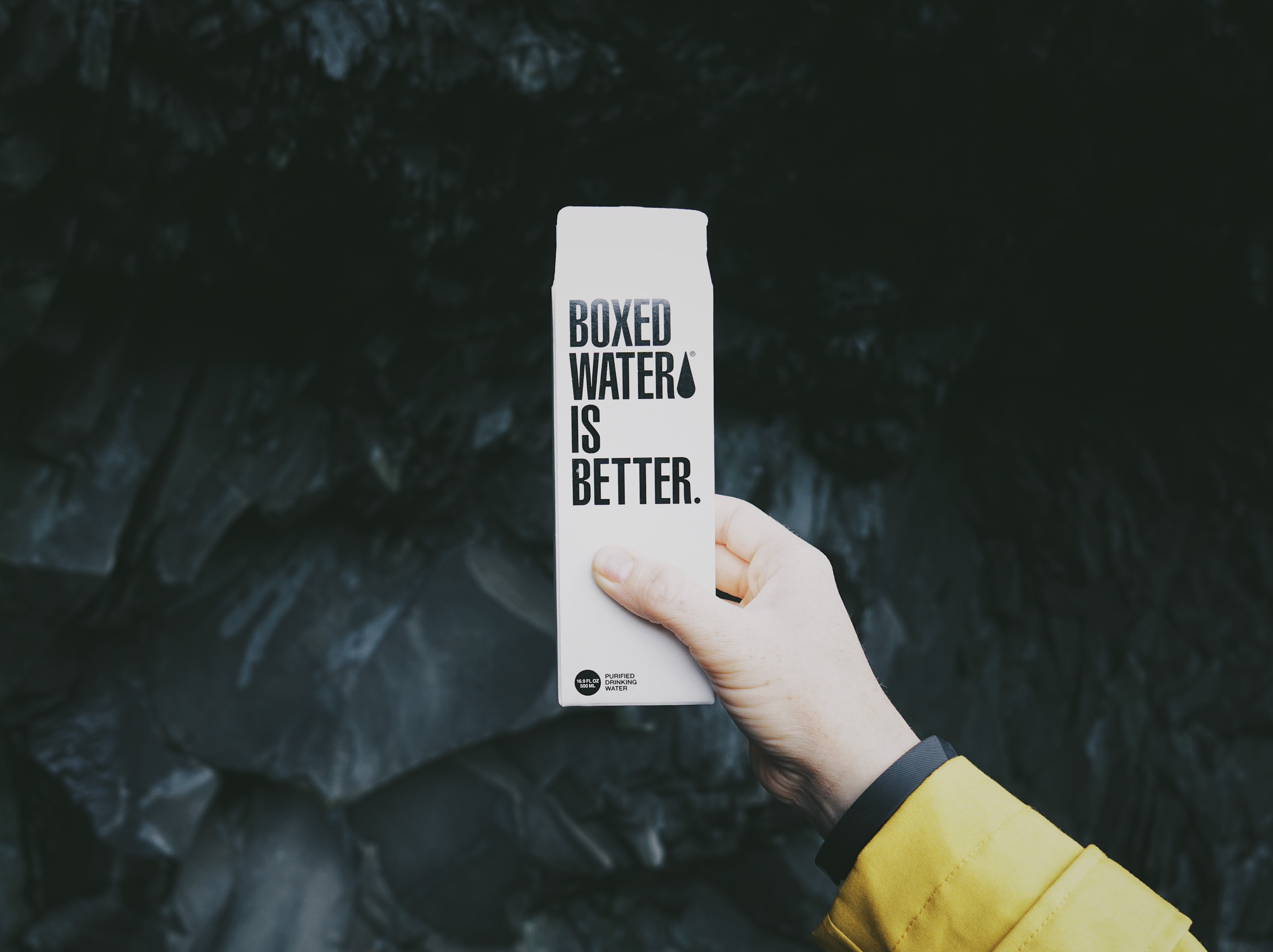 A person holding a white Boxed water is better carton