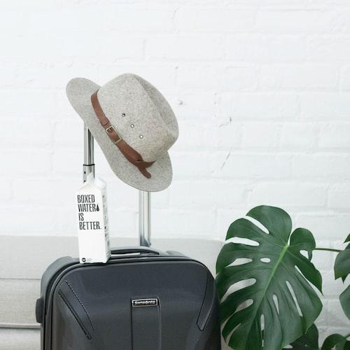 Valise de voyage avec chapeau posé sur la poignée