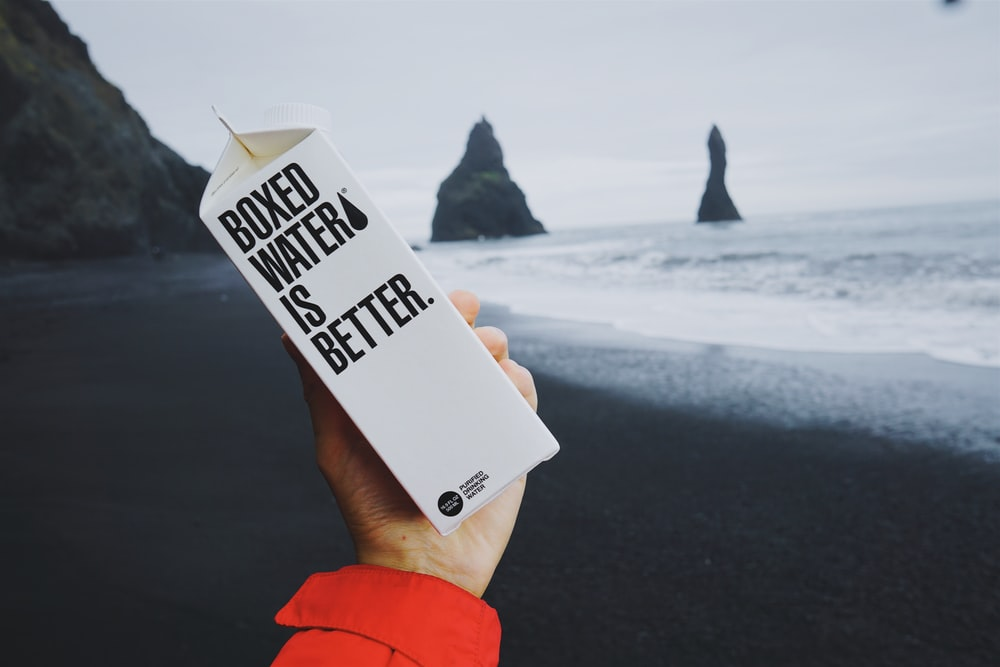 A Boxed Water carton is held by a person in front of an Icelandic beach
