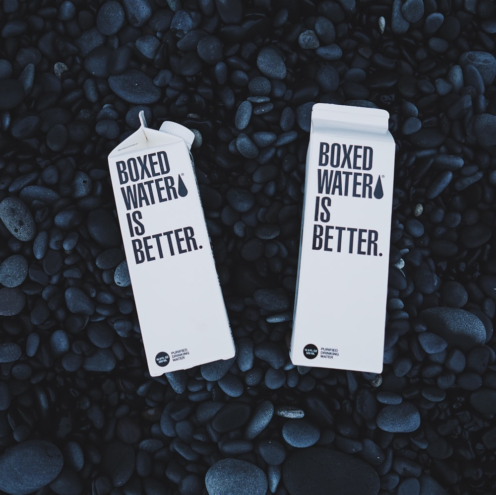 Two Boxed Water cartons on black pebbles