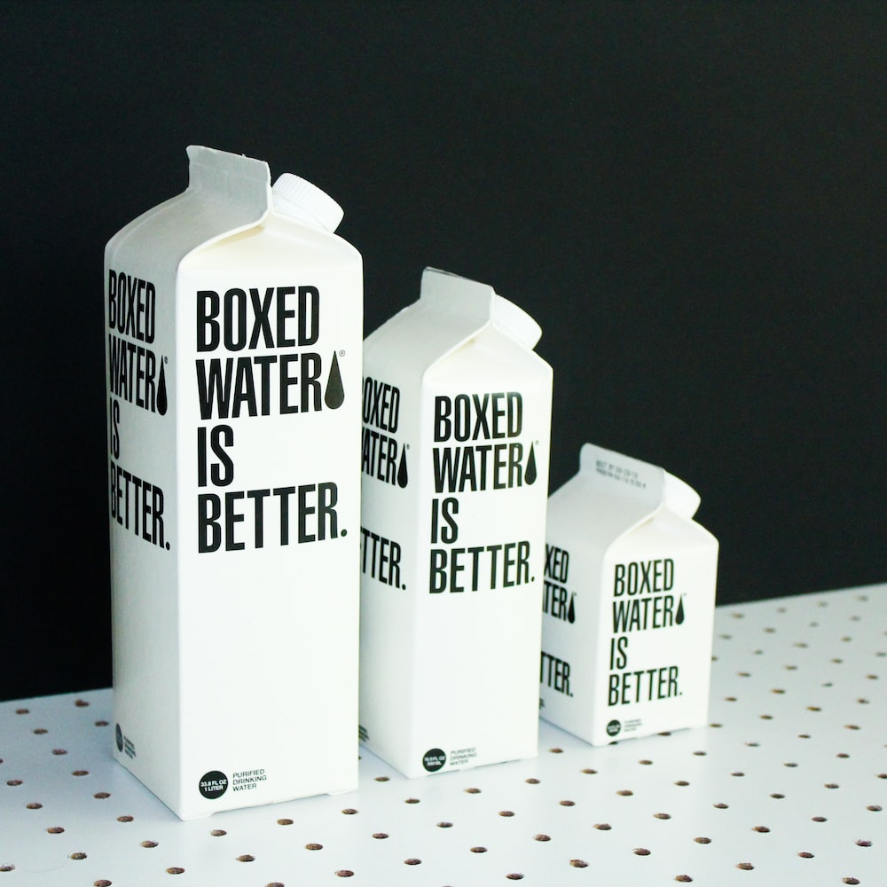 Three different sized Boxed Water cartons on a black and white background