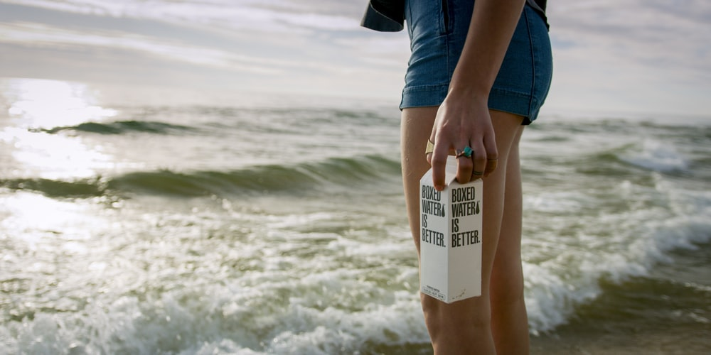 A woman stands in front of waves holding a Boxed Water carton