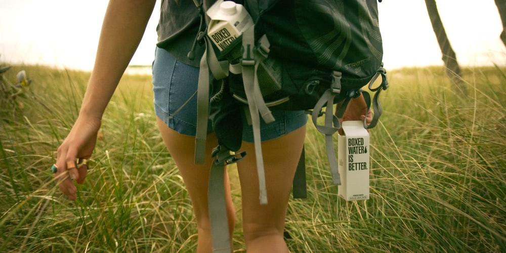 A woman walking in a field holding a Boxed Water carton