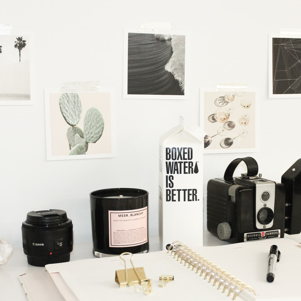 A black camera lens beside a white spring notebook and Boxed Water carton