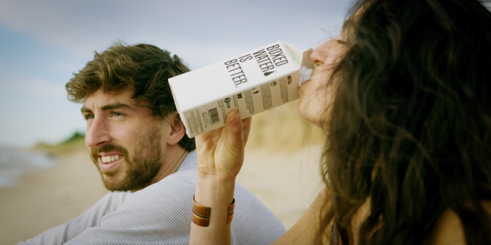 A woman drinking a Boxed Water carton