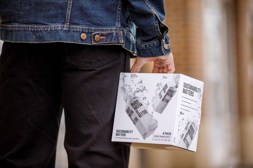 A person carrying a box of Boxed Water