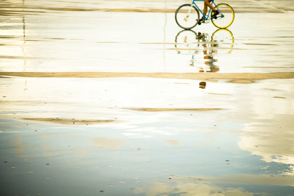 person riding bicycle with reflection to water during daytime